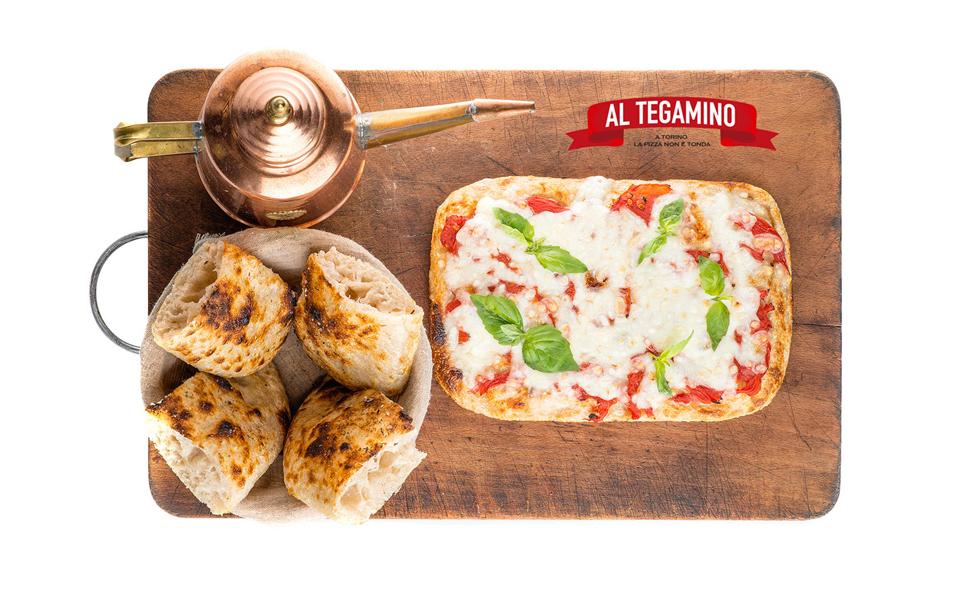 Una pizza su un tagliere con olio per l'immagine coordinata della pizzeria. BwithC