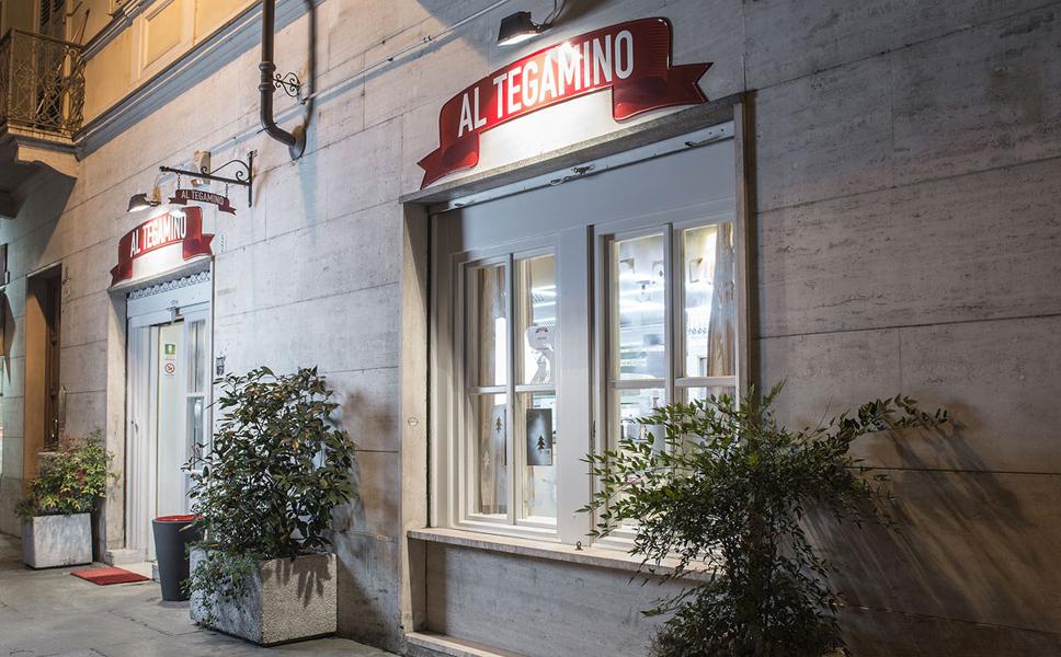 Insegna di una pizzeria di notte a Torino BwithC